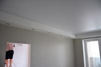 Многоуровневый потолочный короб со светильниками вгостиной, оклейка обоями стен уже завершена